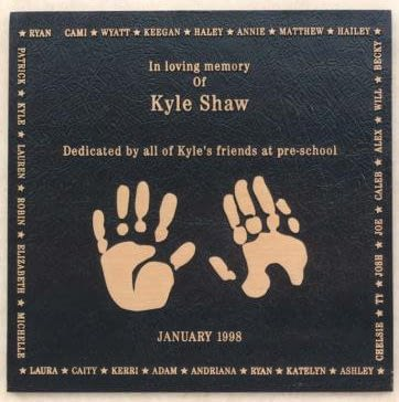 Memorial plaque with baby hand imprints on it.